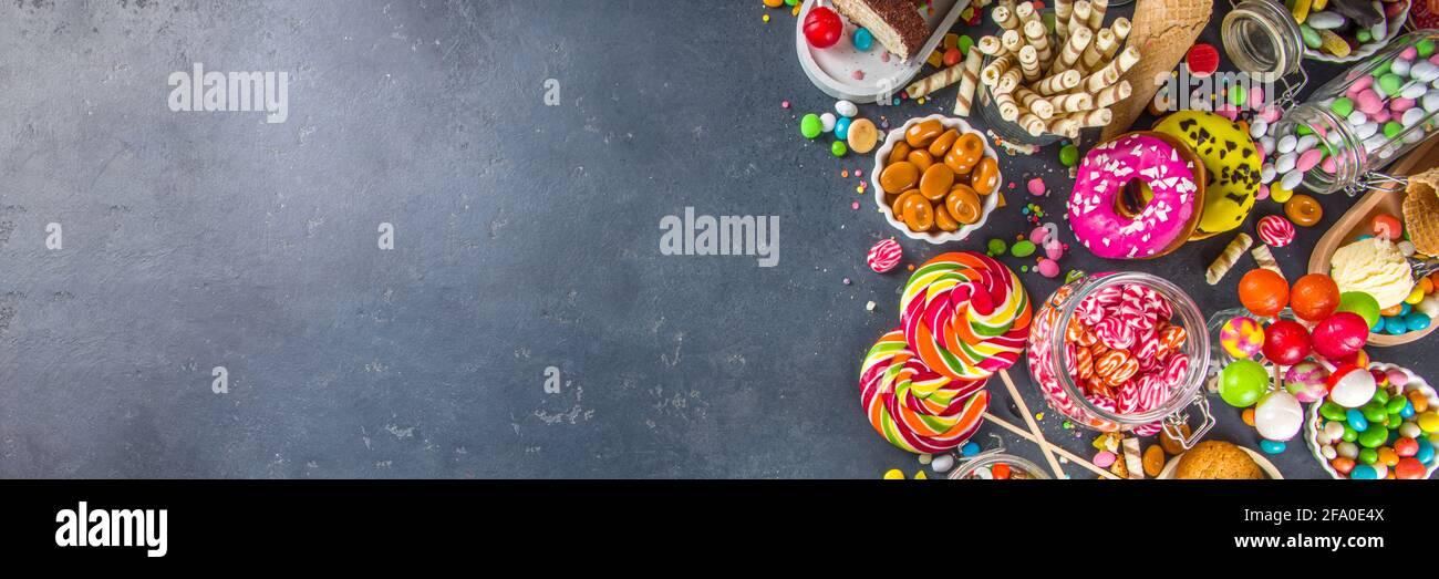 Sélection de bonbons colorés. Assortiment de bonbons, chocolats, beignets, biscuits, sucettes, vue sur le dessus de la glace sur fond de béton noir Banque D'Images