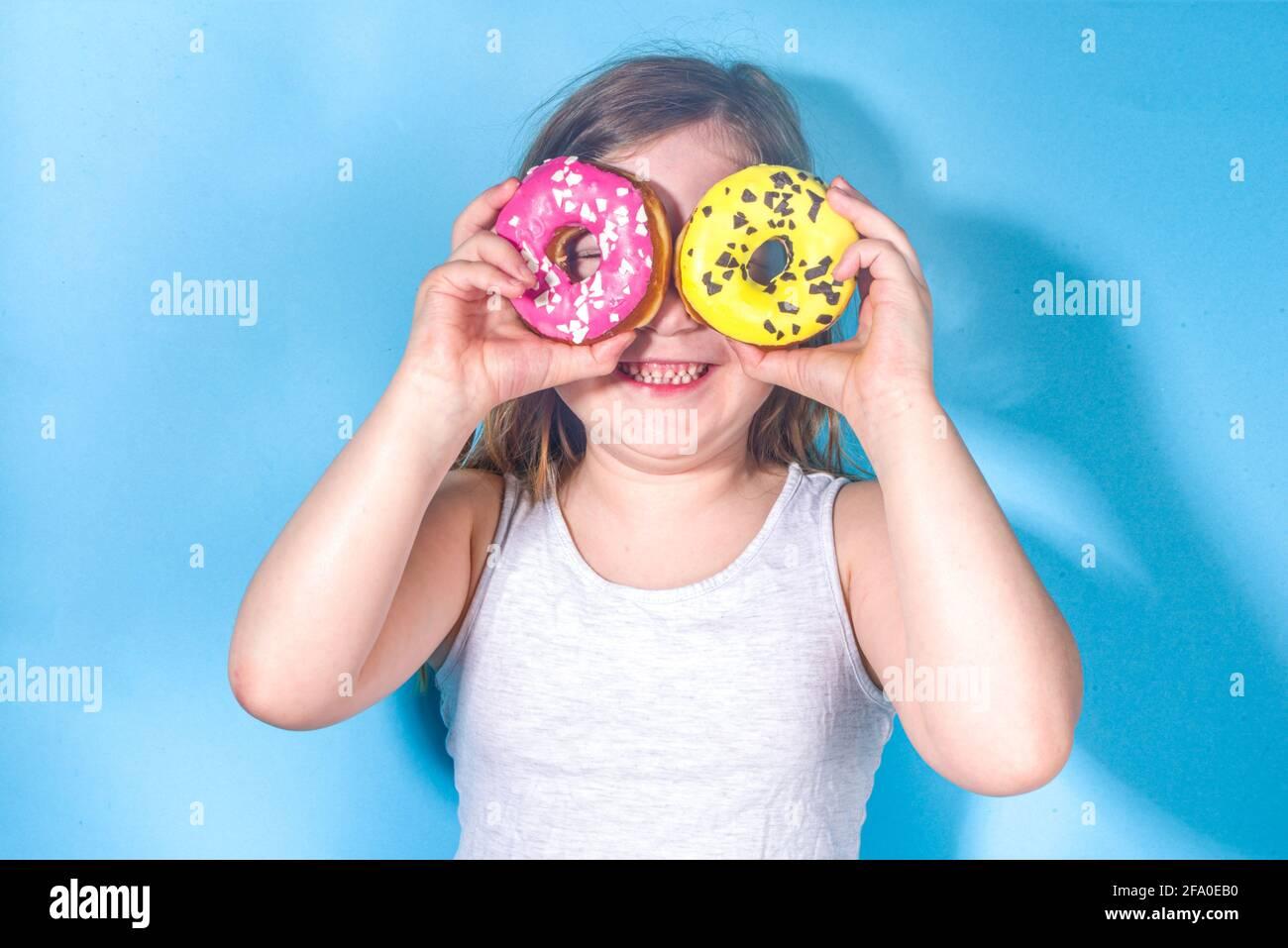 Petite fille drôle heureuse avec sucre coloré glacé de beignets roses et jaunes, vacances, bonheur, concept de vacances d'été, Banque D'Images