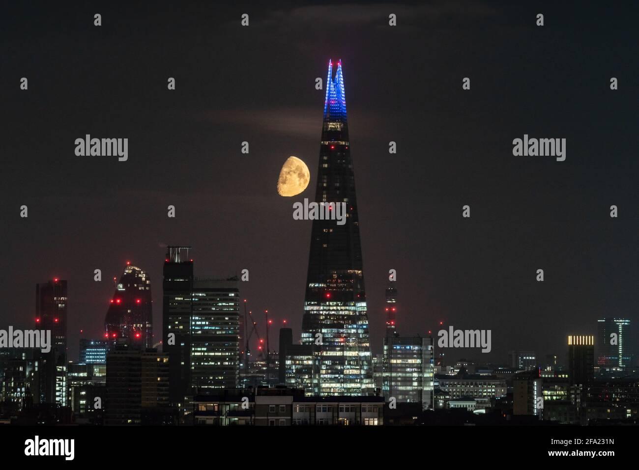Londres, Royaume-Uni. 22 avril 2021. Météo au Royaume-Uni : une lune de Gibbous à 75 % de cire continue de se coucher tôt jeudi derrière le gratte-ciel de Shard, suivant une direction nord-ouest. Credit: Guy Corbishley/Alamy Live News Banque D'Images