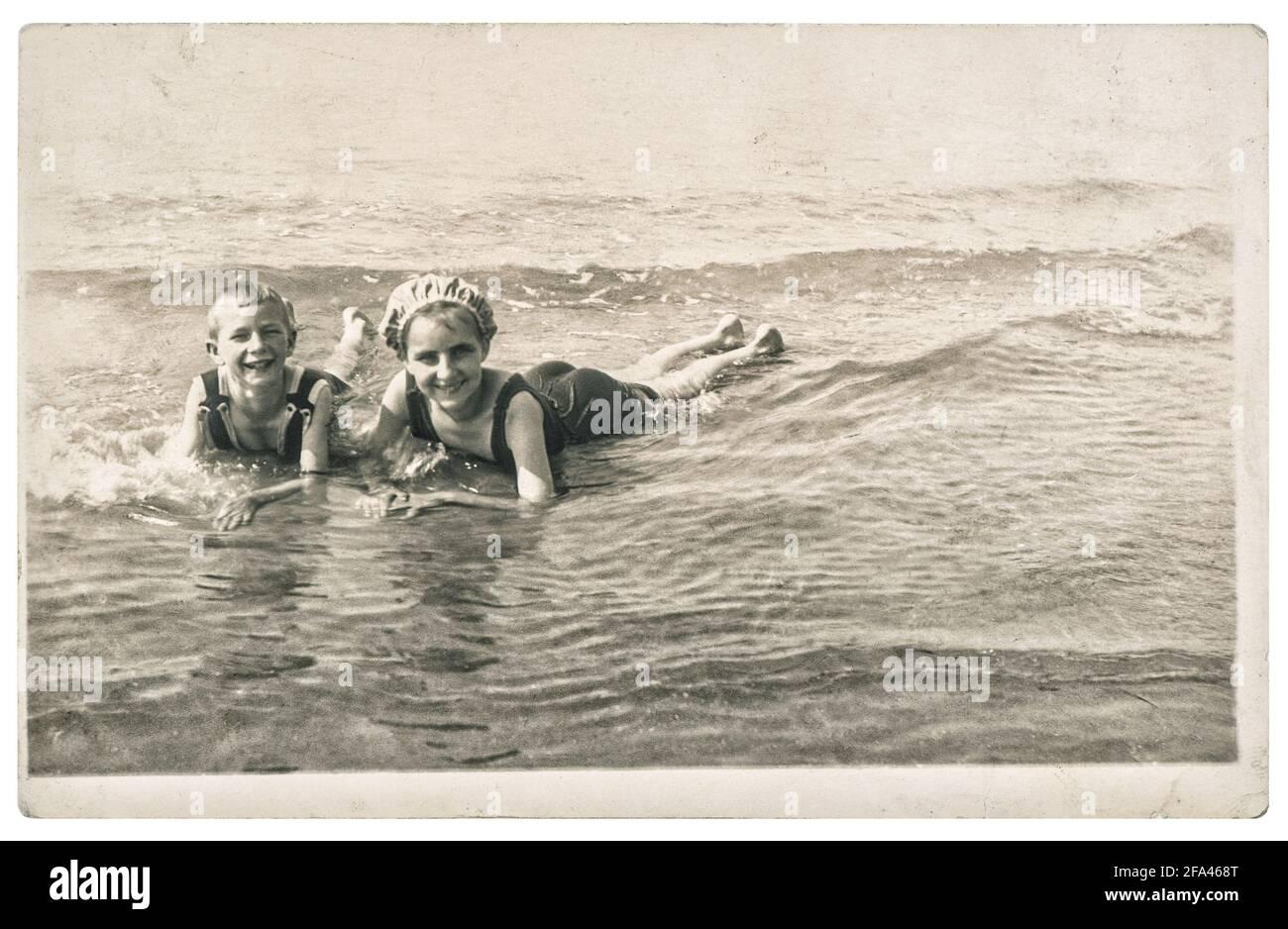 Photo ancienne des enfants sur la mer. Vacances d'été. Image vintage avec grain de film original et flou ca. 1920 Banque D'Images