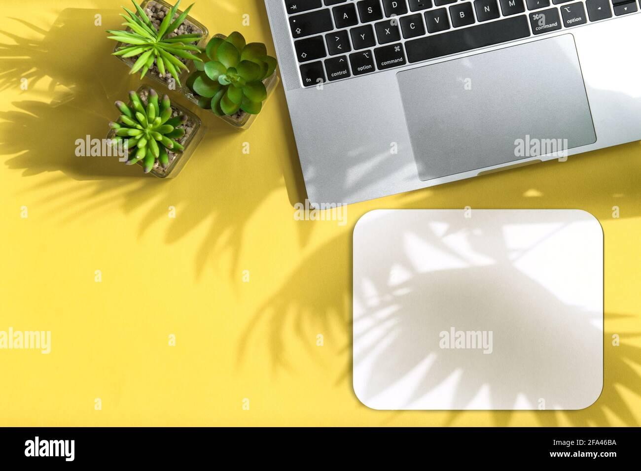 Bureau à domicile, plan de travail. Ordinateur portable et tapis de souris avec ombre au soleil Banque D'Images