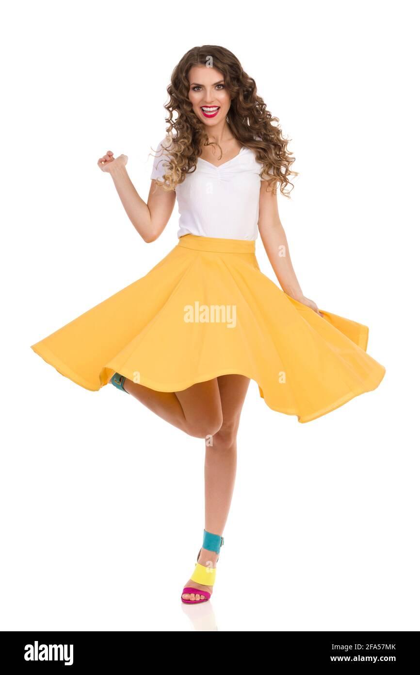 Belle jeune femme en jupe jaune, haut blanc et hauts talons hauts colorés chante sur une jambe et chante. Prise de vue en studio sur toute la longueur isolée sur blanc. Banque D'Images