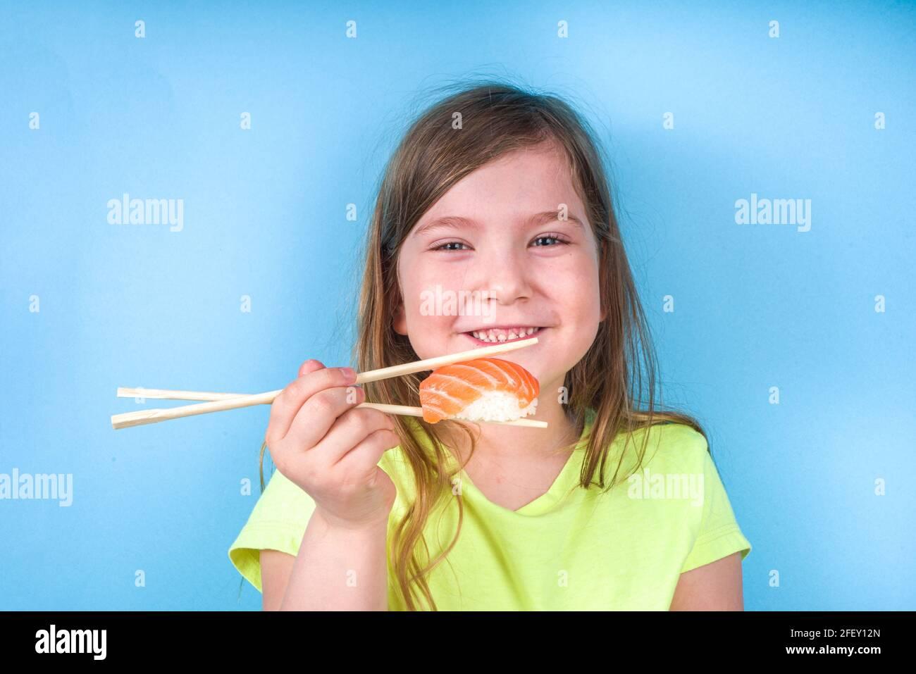 Une petite fille adorable aime manger des sushis. Joyeux drôle caucasien blonde petite fille avec divers rouleaux de sushi et baguettes. Sur fond bleu vif Banque D'Images