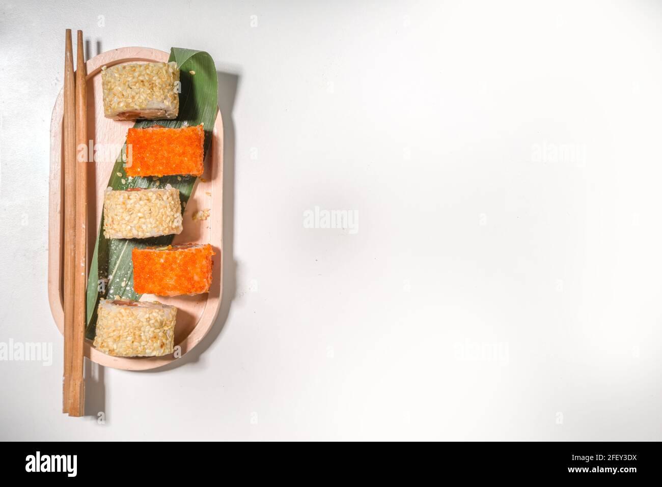 Petits pains à sushi, riz et poisson, sauce soja sur fond blanc Banque D'Images