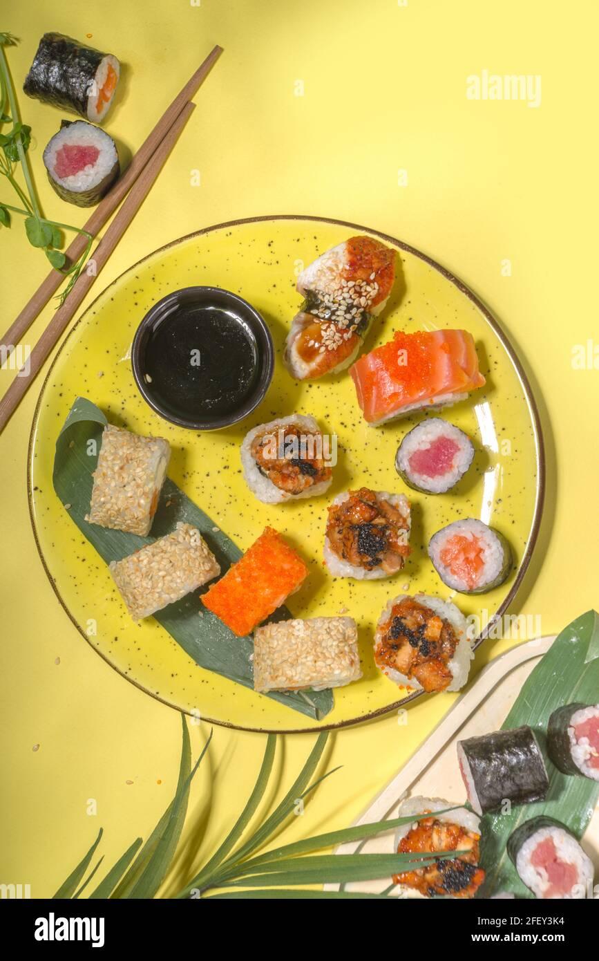 Petits pains à sushi avec riz et poisson, sauce soja et baguettes sur fond jaune, plat tendance à la lumière du jour Banque D'Images