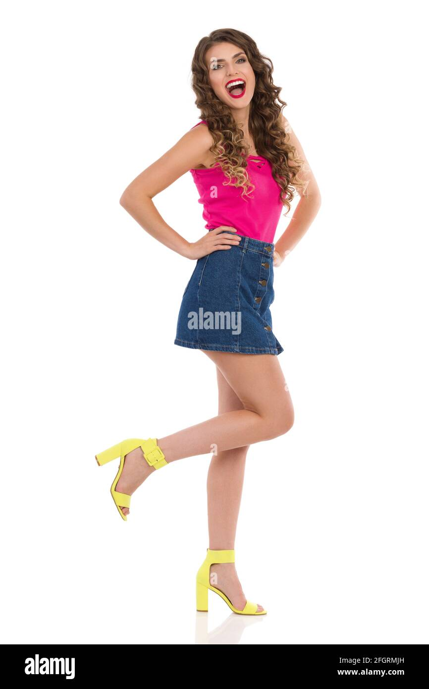 Belle jeune femme en Jean mini jupe, rose haut et talons hauts est debout sur une jambe et riant. Prise de vue en studio sur toute la longueur isolée sur blanc. Banque D'Images