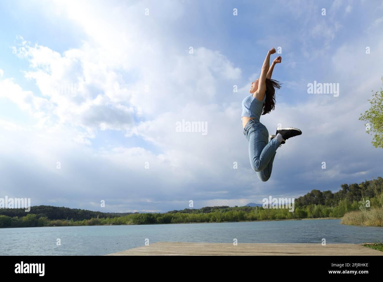 Profil d'une femme heureuse sautant dans un lac célébrant Banque D'Images