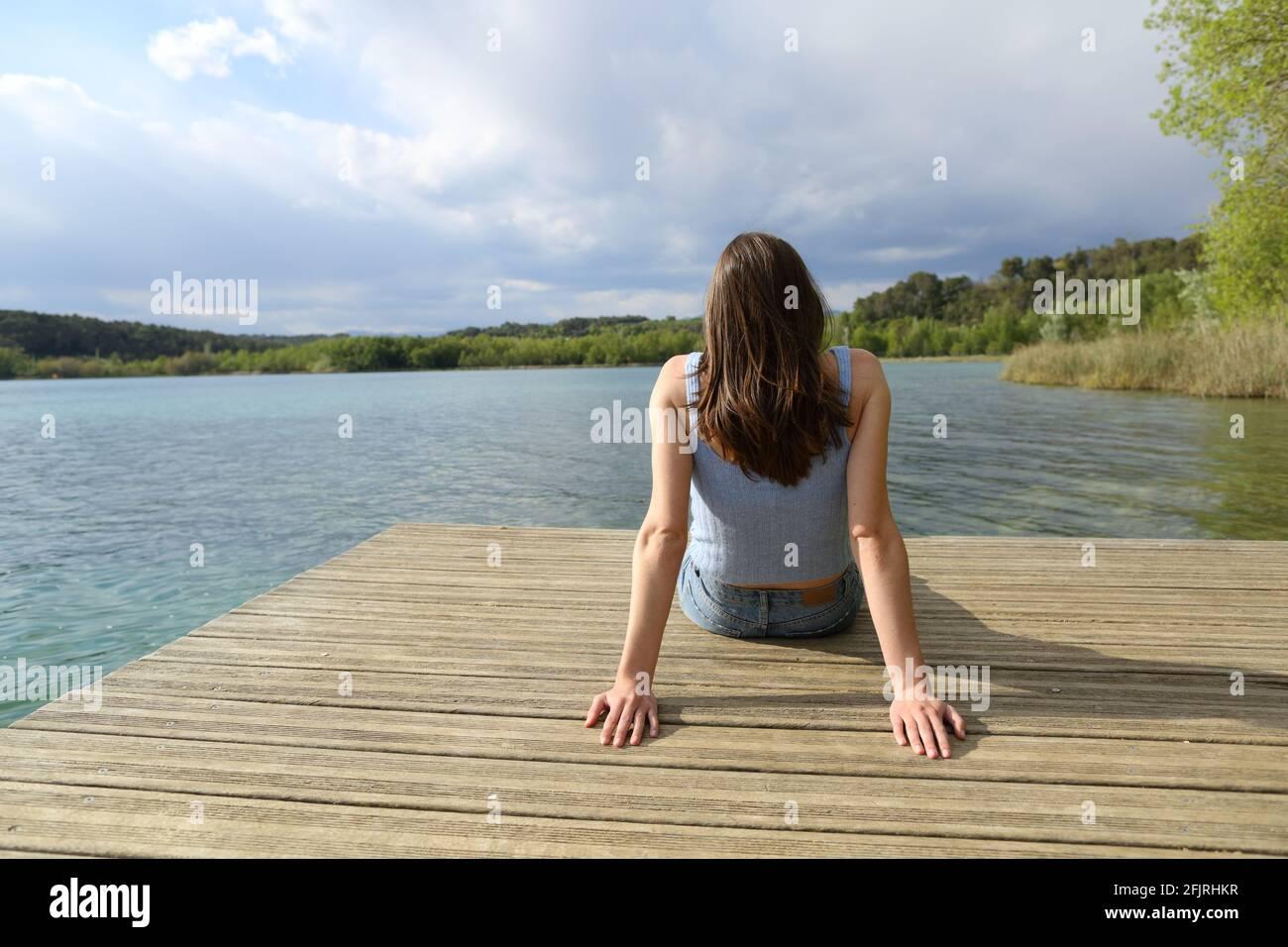 Vue arrière portrait d'une femme assise relaxante dans un lake pier en vacances d'été Banque D'Images