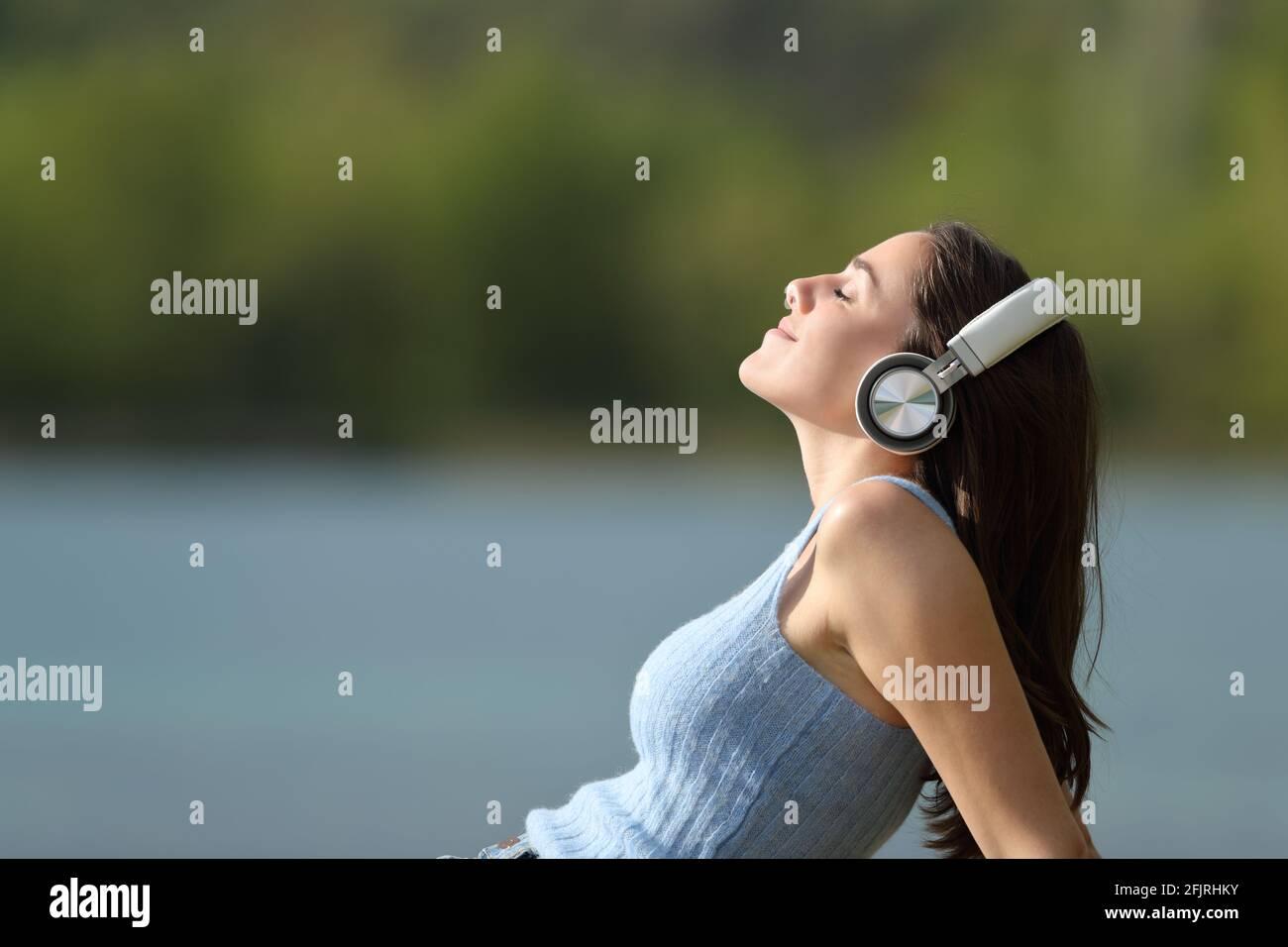 Portrait d'une femme décontractée portant un casque d'écoute sur le côté à la musique dans un lac Banque D'Images