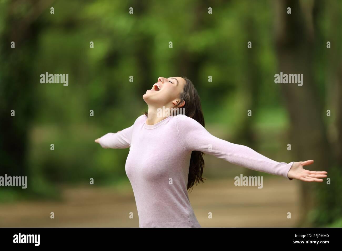 Une femme excitée qui se dépasse les bras et qui crie dans une forêt célébrant vacances Banque D'Images