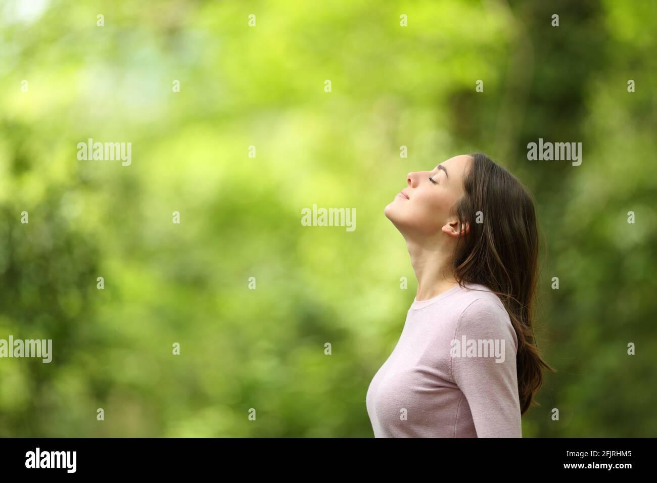Profil d'une femme détendue respirant de l'air frais dans un forêt verte Banque D'Images