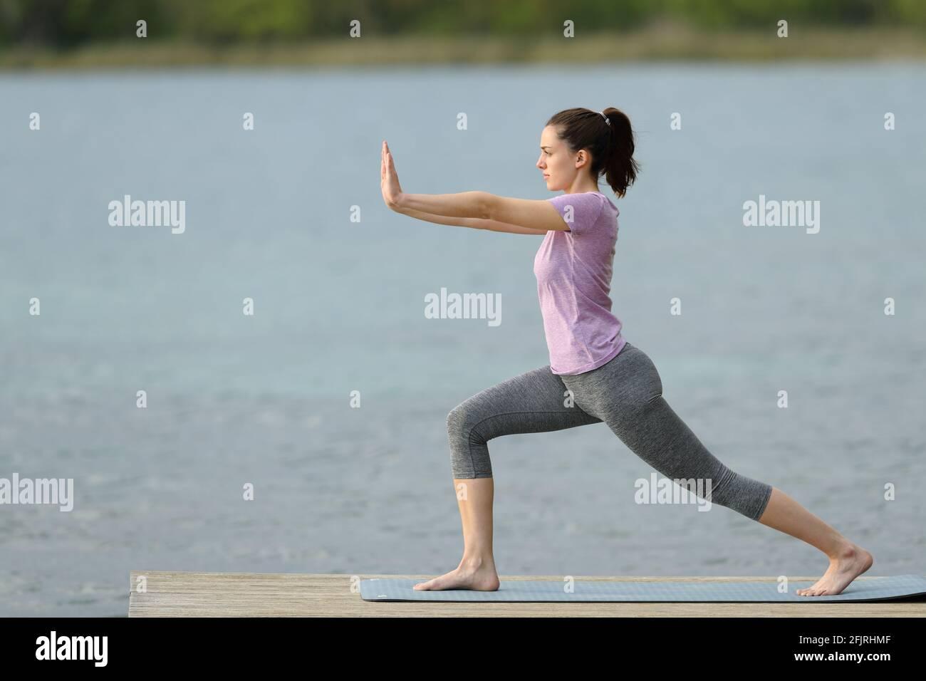 Vue latérale d'une femme effectuant un exercice de tai chi en été, dans une jetée de lac Banque D'Images