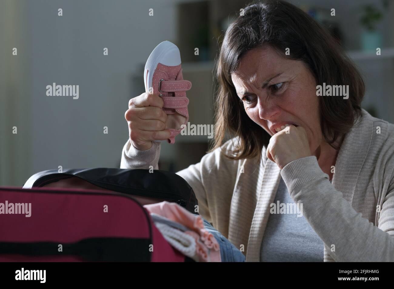 Femme adulte divorcée en colère regardant le sac de week-end de fille désorganisé la nuit à la maison Banque D'Images