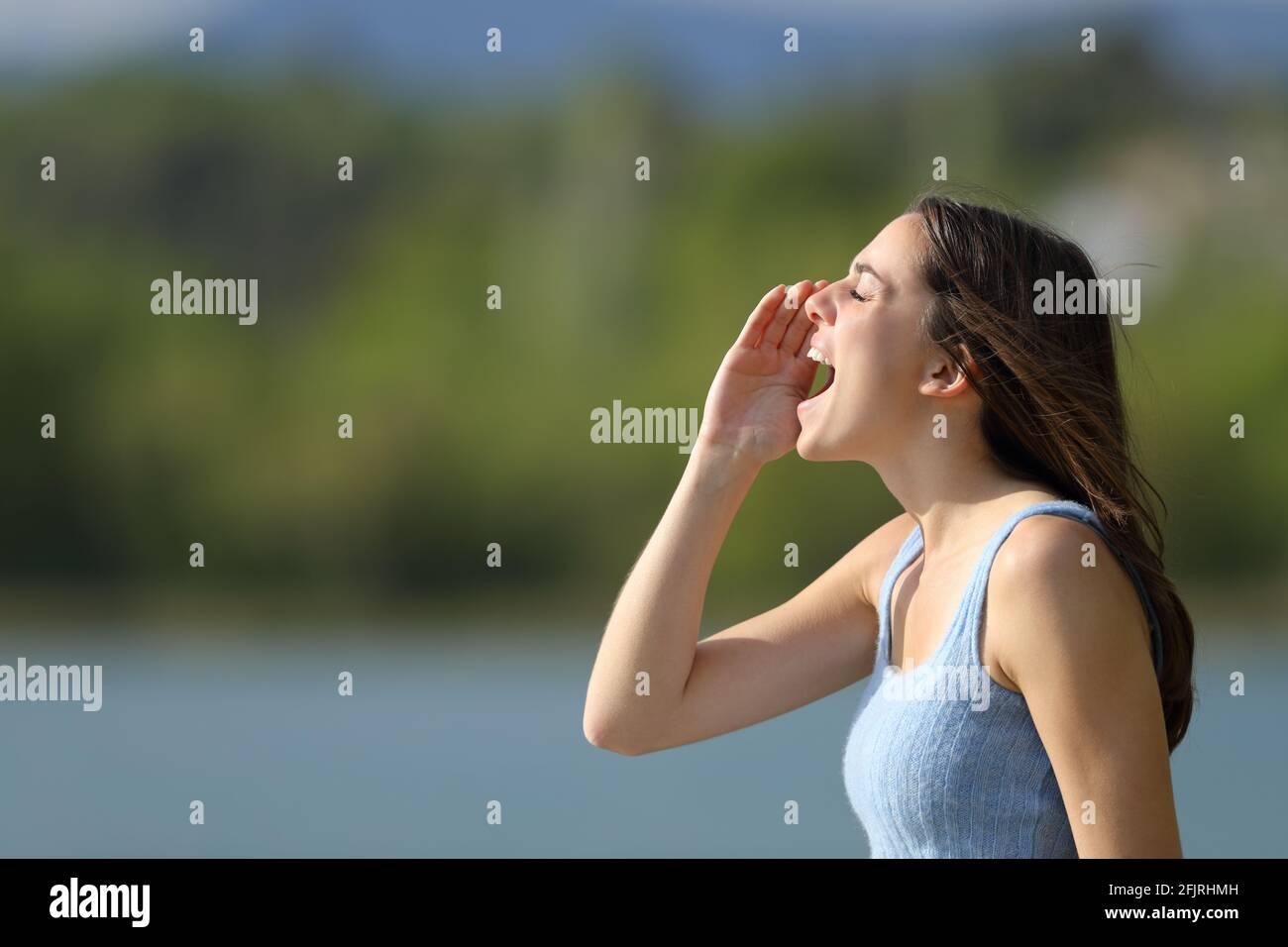 Profil d'une femme hurlant dans un lac l'été Banque D'Images