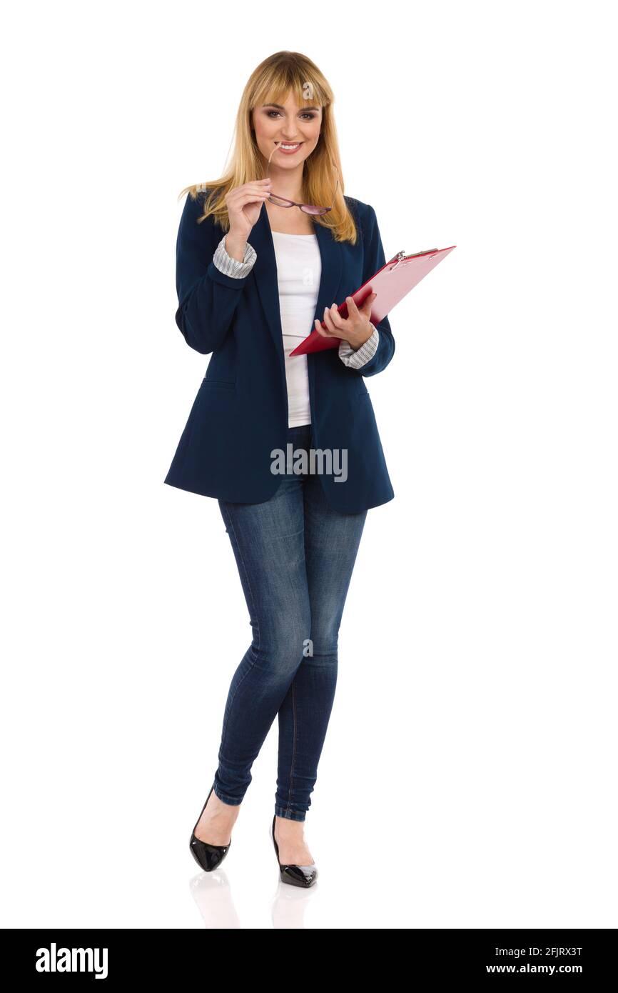 Belle jeune femme en costume bleu, jeans et talons hauts est debout avec le presse-papiers et sourire. Prise de vue en studio pleine longueur isolée sur fond blanc. Banque D'Images