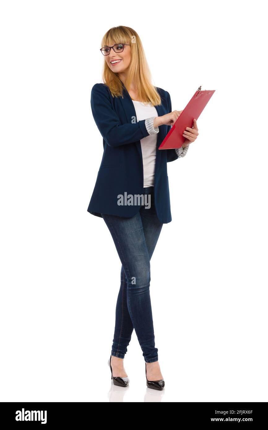 Belle jeune femme en costume bleu, jeans et talons hauts est debout et tenant le presse-papiers et regardant loin au-dessus de l'épaule. Prise de vue en studio Banque D'Images