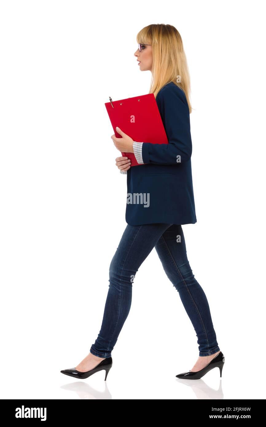 Jeune femme d'affaires en costume bleu et talons hauts marche avec presse-papiers. Vue latérale. Prise de vue en studio pleine longueur isolée sur fond blanc. Banque D'Images