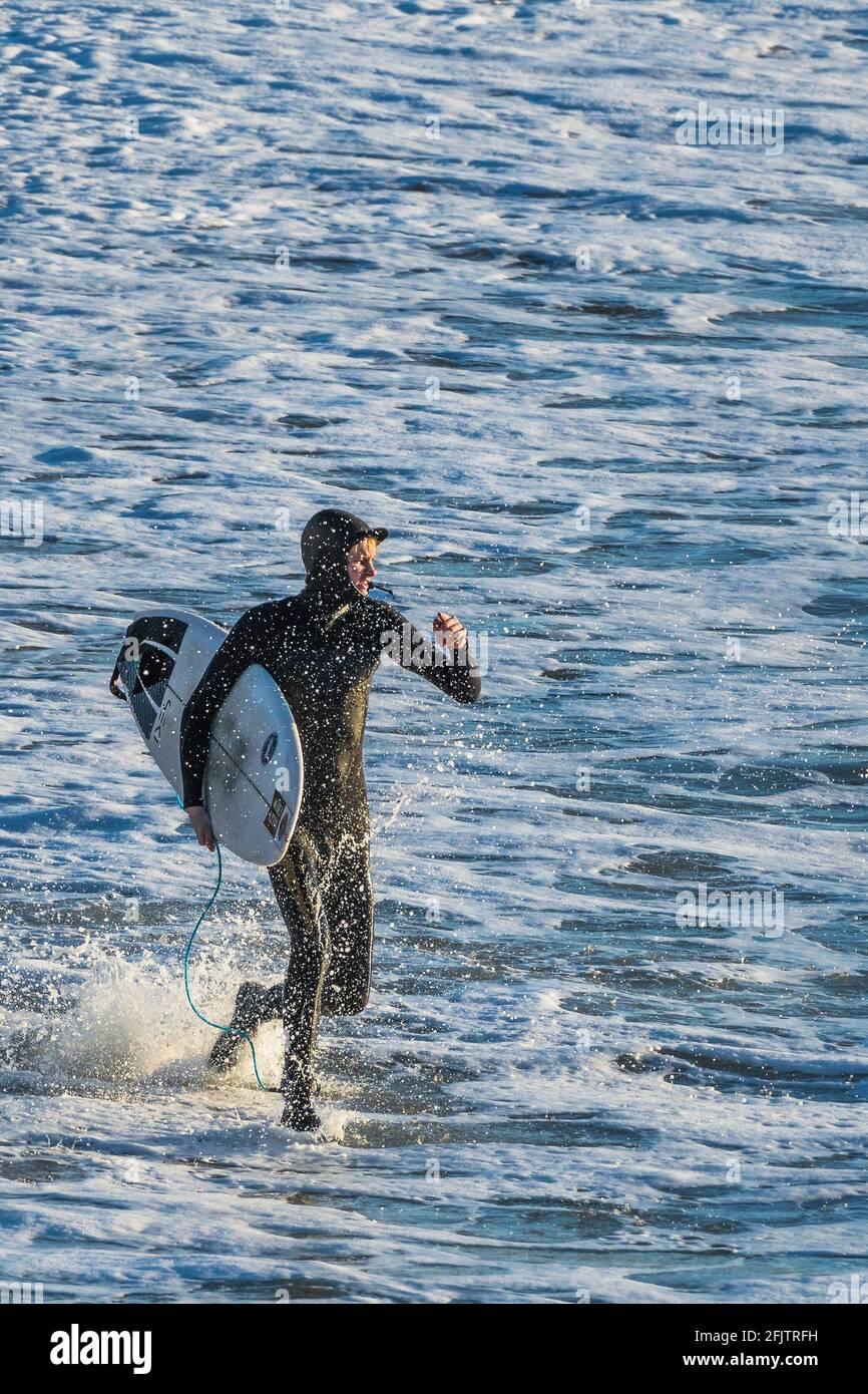 Un surfeur vif transportant son surf et courant dans la mer à Fistral à Newquay en Cornouailles. Banque D'Images