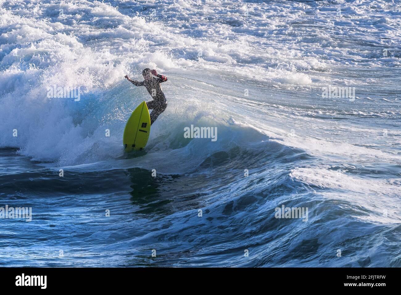 Un surfeur qui s'aprise d'une vague à Fistral, à Newquay, en Cornouailles. Banque D'Images