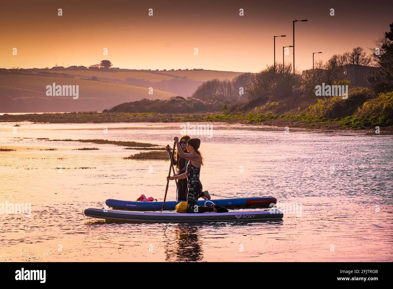 Feu d'or en soirée, deux planchistes femelles sur les paddleboards Stand Up paddle à marée haute sur la rivière Gannel à Newquay dans les Cornouailles. Banque D'Images