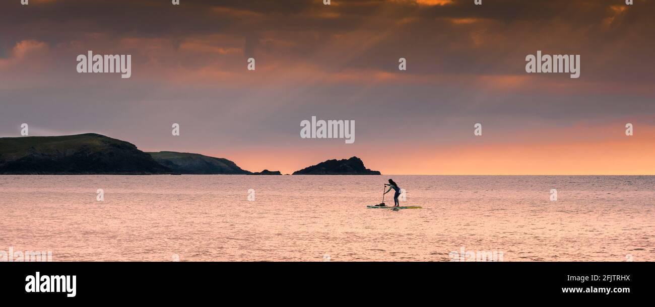 Image panoramique d'une femelle debout Paddleboarder pagayant pendant un coucher de soleil doré dans la baie de Fistral à Newquay en Cornouailles. Banque D'Images