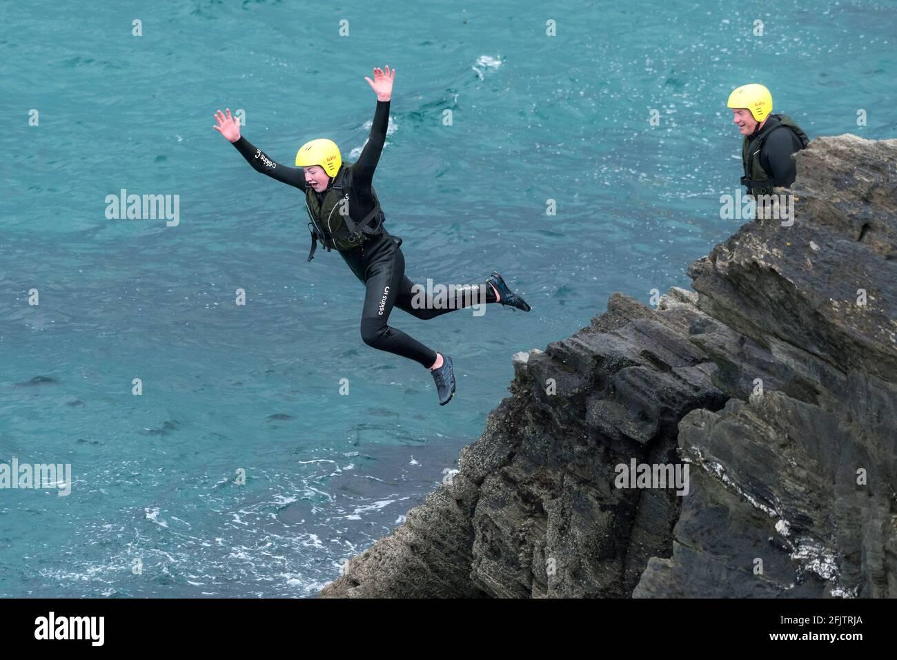 Un jeune vacanciers sautant dans la mer depuis les rochers lors d'un voyage en bateau autour de Towan Head à Newquay, en Cornouailles. Banque D'Images