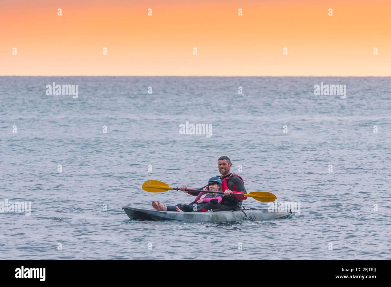 Un holidaymaker et sa jeune fille sur un kayak de GoSea sit-on-Top dans la mer à la lumière du soir à Little Fistral à Newquay en Cornouailles. Banque D'Images