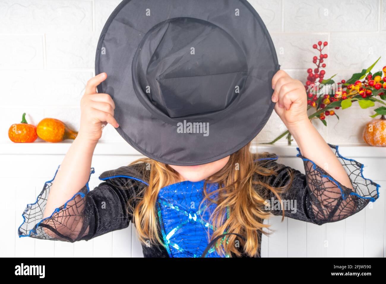 Vacances d'automne Halloween arrière-plan. Bonne fille caucasienne dans une robe et un chapeau de sorcière, avec des seaux de bonbons dans la maison ou un espace de copie de jardin d'enfants Banque D'Images
