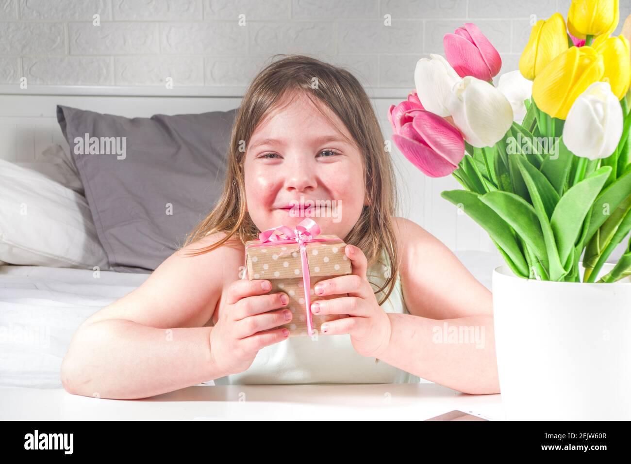 Fête des mères, fête des filles concept de style de vie. Enfant jeune fille blonde jeune fille avec un bouquet de fleurs de tulipe, carte de vœux faite à la main Banque D'Images