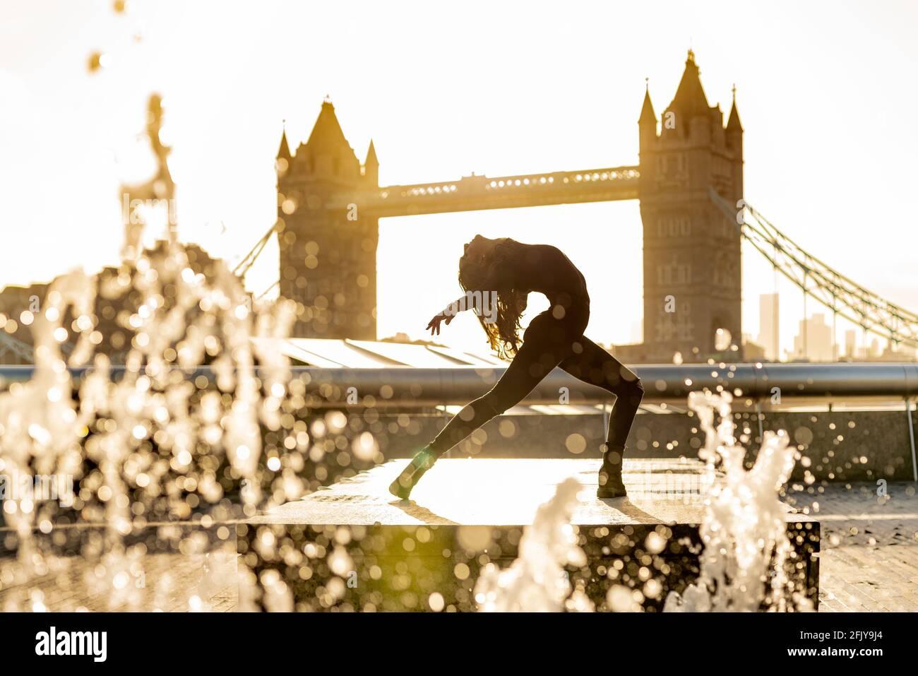 Londres, Royaume-Uni. 27 avril 2021. Journée internationale de la danse : Rebecca Olarescu, étudiante en Master Screance à la London Contemporary Dance School (LCDS), se produit lors d'un lever de soleil spectaculaire aux fontaines près de Tower Bridge, en prévision de la Journée internationale de la danse, le 29 avril. Célébrée pour la première fois en 1982, la Journée internationale de la danse a lieu chaque année depuis l'anniversaire de la naissance de Jean-Georges Noverre (1727-1810), créateur du ballet moderne. Credit: Guy Corbishley/Alamy Live News Banque D'Images