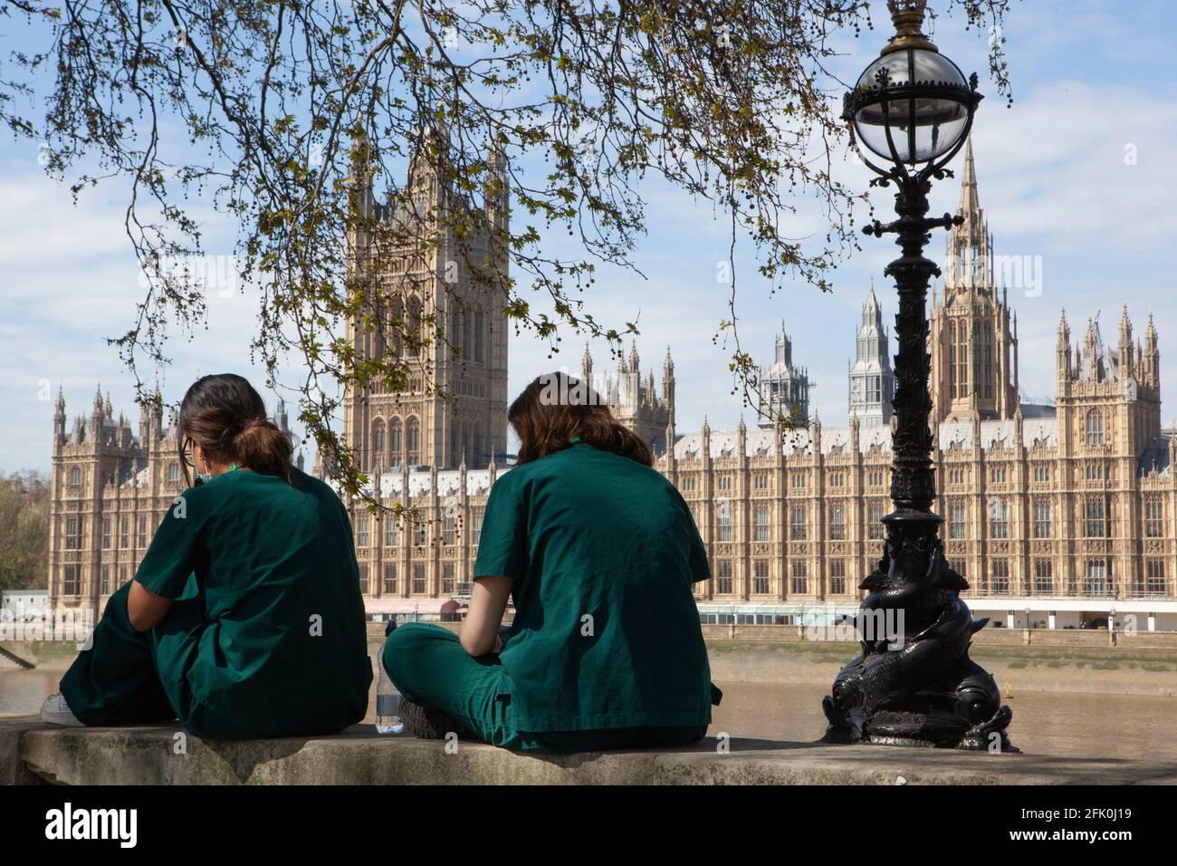 Londres, Royaume-Uni, 27 avril 2021 : les médecins étudiants Charlie et Surina prennent une pause au-dessus du mur commémoratif national Covid alors que le Premier ministre Boris Johnson est toujours accusé d'avoir préféré que les « corps s'accumulent » plutôt que d'avoir un troisième verrouillage. Avec un coeur dessiné pour chacun des plus de 150,000 personnes qui sont mortes dans la pandémie de coronavirus au Royaume-Uni, le mémorial s'étend le long du mur de l'hôpital St Thomas, en face du Parlement sur la rive opposée de la Tamise. Anna Watson/Alay Live News Banque D'Images