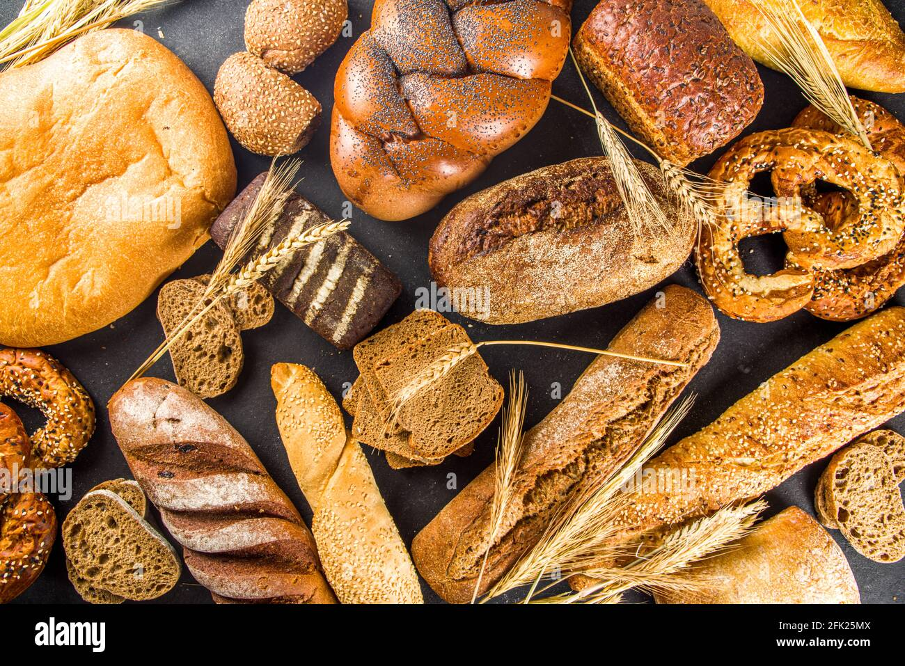 Assortiment de délicieux pains fraîchement cuits, sur fond de béton noir vue du dessus de l'espace de copie Banque D'Images
