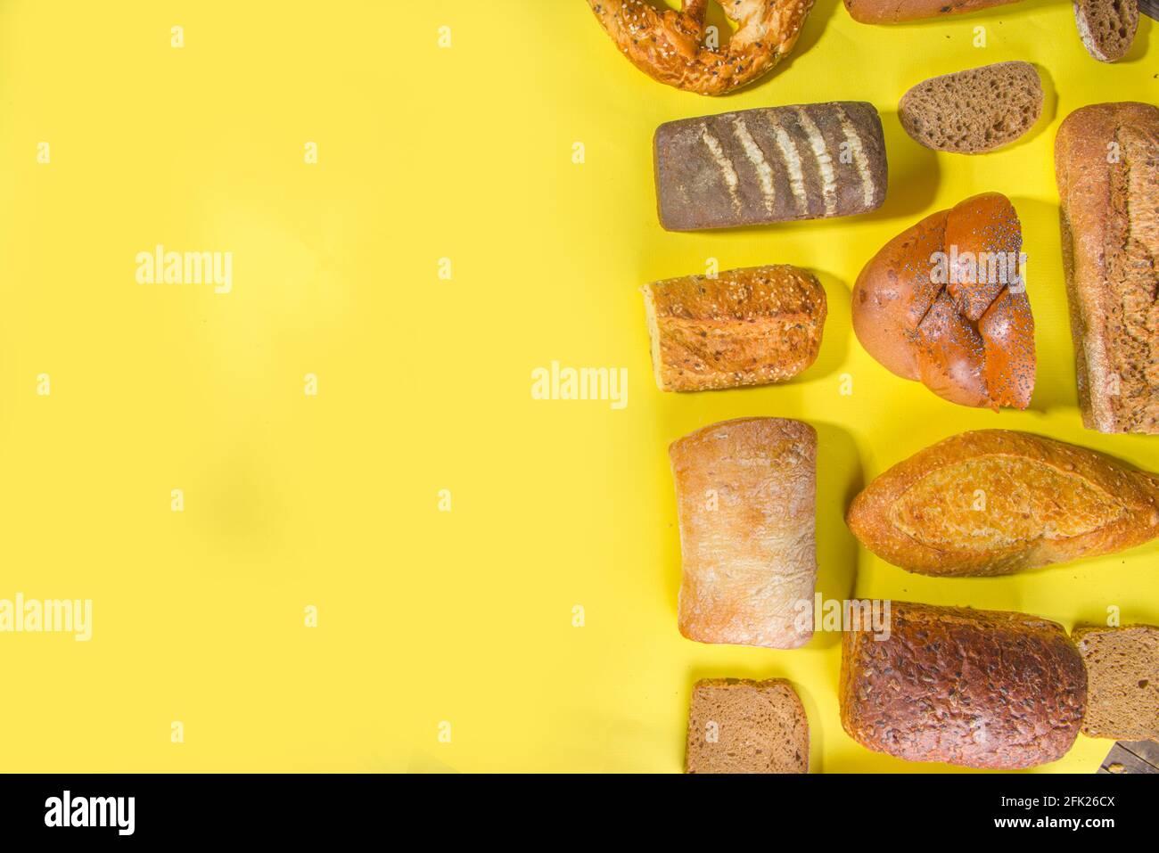 Assortiment de délicieux pains fraîchement cuits, sur fond lumineux et tendance, espace de copie avec vue de dessus, motif sur jaune Banque D'Images