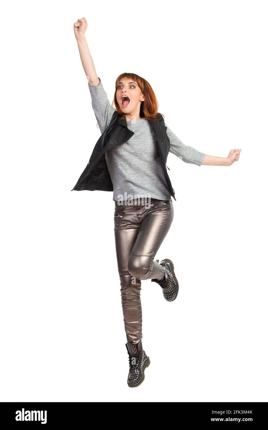 Une jeune femme en blouse grise, pantalon brillant et bottes noires saute avec le bras relevé et criant. Prise de vue en studio sur toute la longueur isolée sur blanc. Banque D'Images