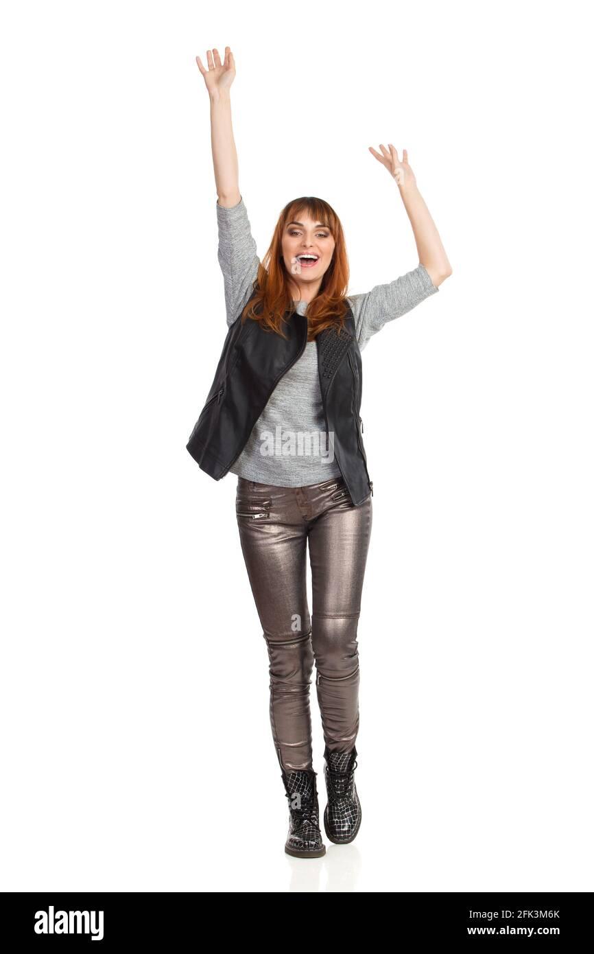 Jeune femme heureuse en blouse grise, pantalon brillant et bottes noires est debout avec les bras relevés et les mains de signe. Vue avant. Prise de vue en studio pleine longueur isola Banque D'Images