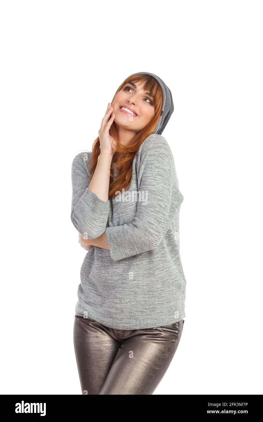 Une jeune femme souriante en blouse grise, pantalon brillant et casquette d'hiver est à la recherche. Vue avant. Trois quarts de longueur en studio prises isolées sur blanc. Banque D'Images