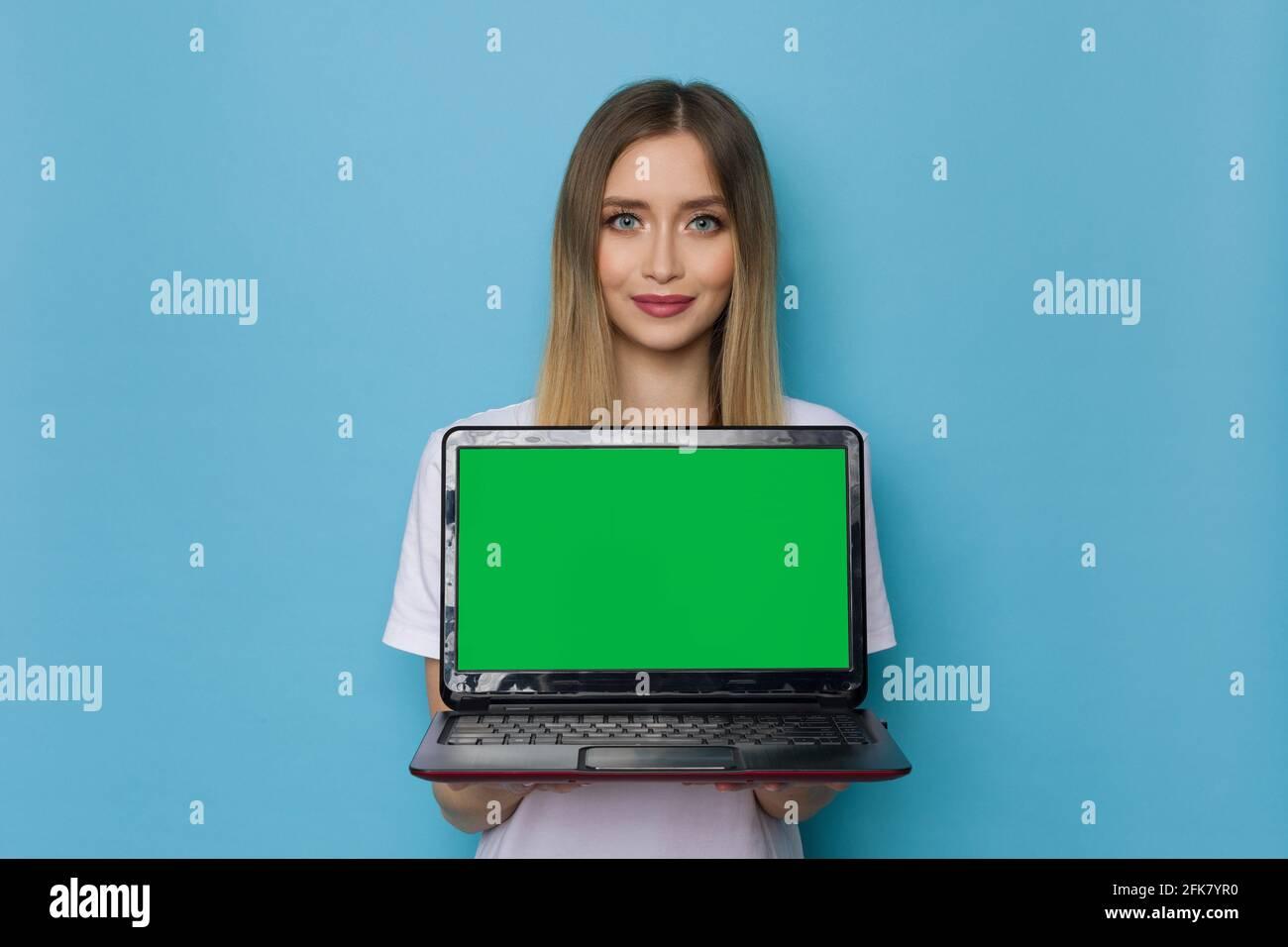 Belle jeune femme tient un ordinateur portable avec un cri vert. Taille haute studio tourné sur fond bleu. Banque D'Images