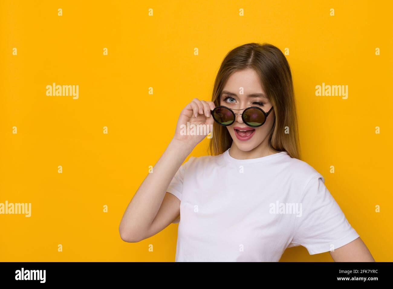 Curieuse jeune femme blonde en chemise blanche est regarder loin au-dessus de lunettes de soleil et de wencrage. Taille haute studio tourné sur fond jaune. Banque D'Images