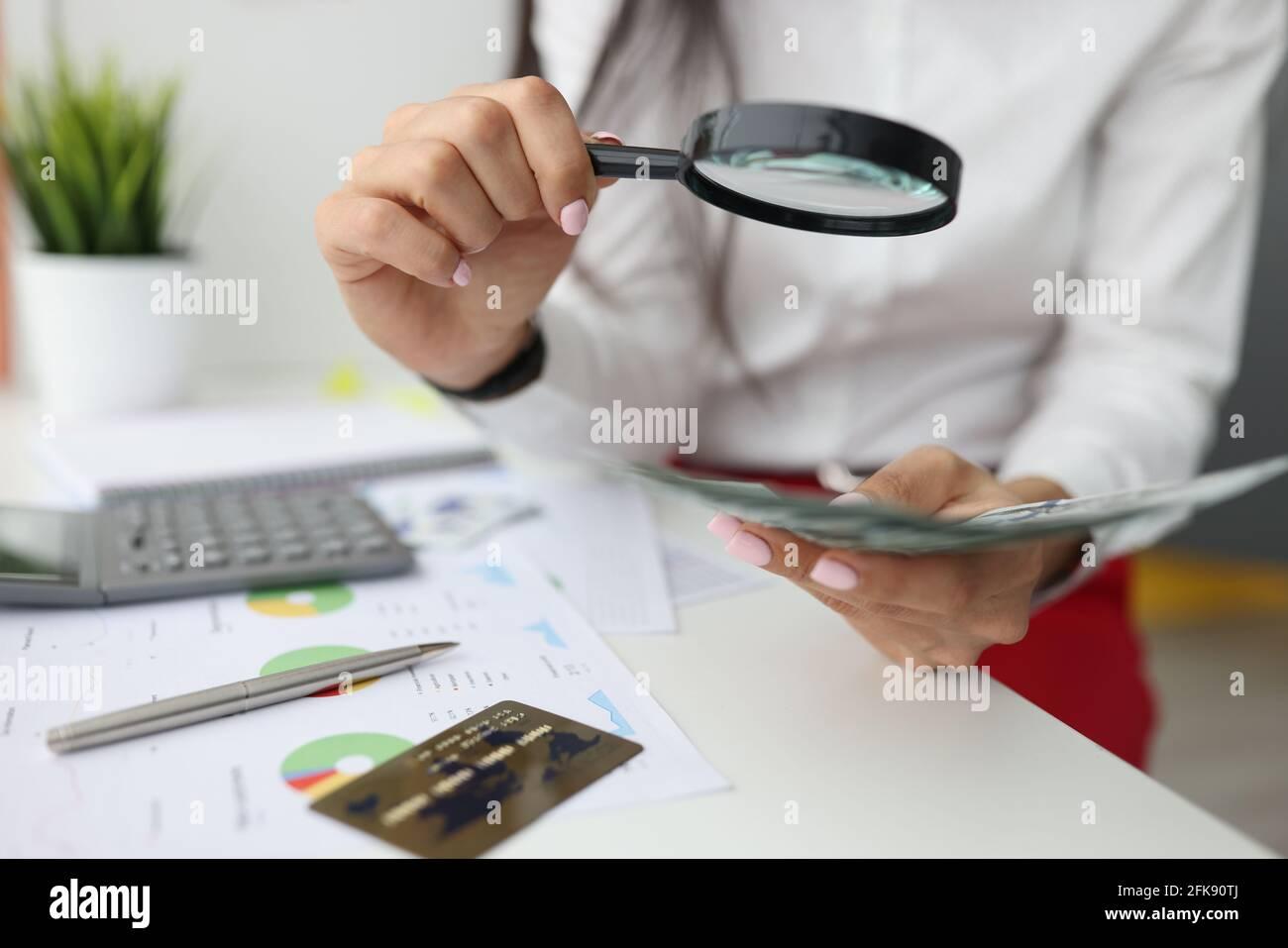La main féminine tient la loupe et l'argent à la table de travail Banque D'Images