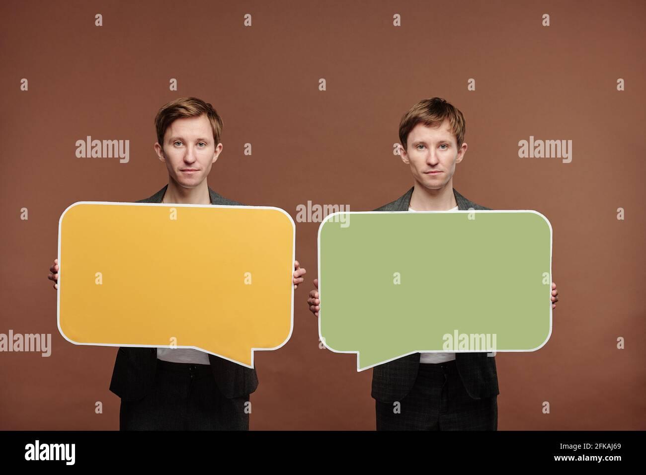 Portrait du contenu frères jumeaux debout sur fond marron et contient des étiquettes à bulles de parole colorées Banque D'Images