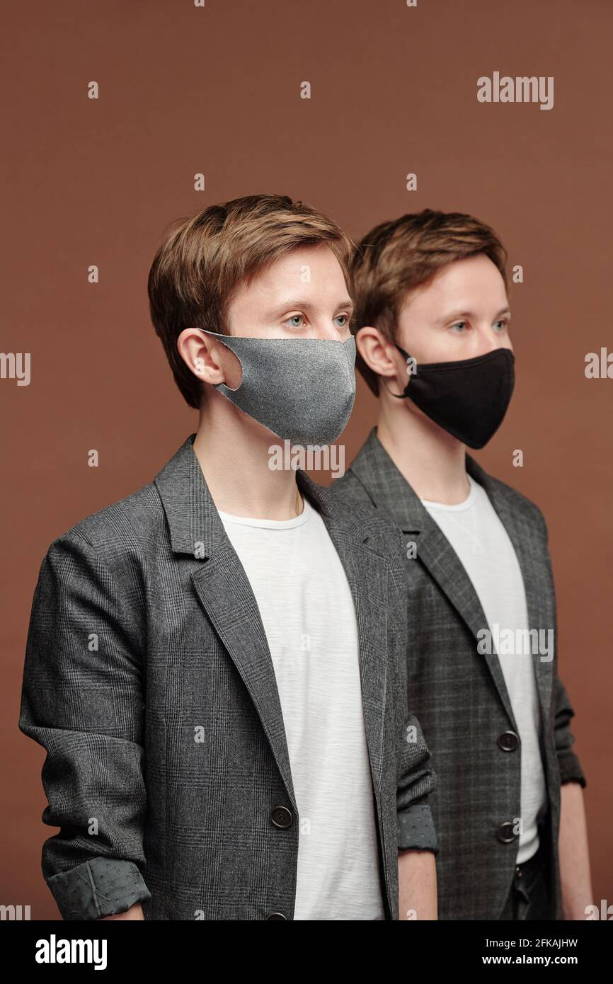 Rangée de jeunes jumeaux doués en costume gris et masques en tissu qui travaillent dans le domaine des affaires Banque D'Images