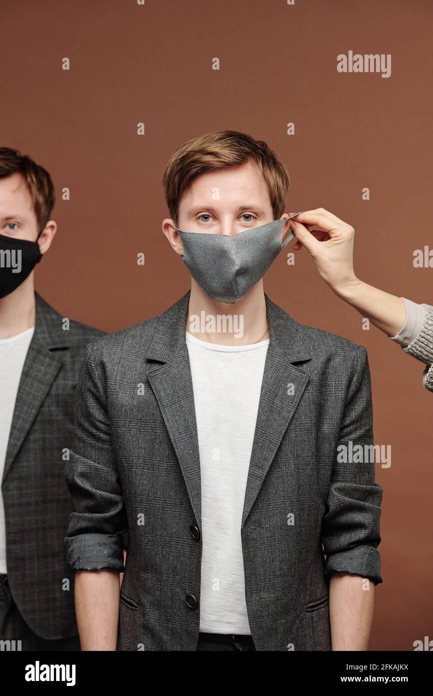Main mettant le masque sur l'oreille de jeune gars en gris costume debout avec frère jumeau sur fond marron Banque D'Images