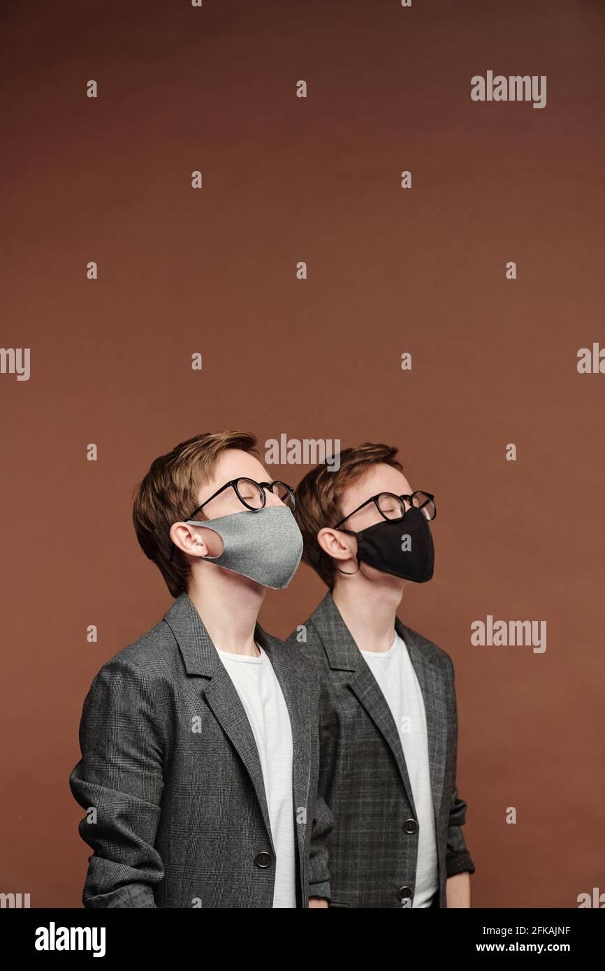 Rangée de deux frères jumeaux dans des masques en tissu et des verres garder les yeux fermés et se tenir contre le fond marron pendant le coronavirus restrictions Banque D'Images