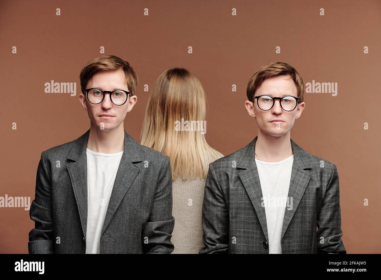 Portrait de jeunes jumeaux sérieux en costumes gris et lunettes debout contre la femme, concept de relation Banque D'Images
