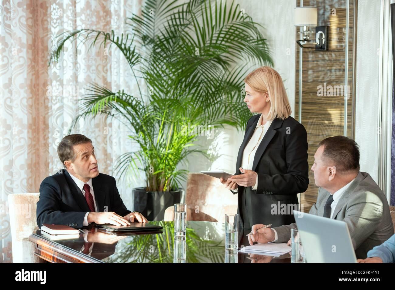 Quelques personnes assises à une table pendant la discussion de conditions de partenariat Banque D'Images
