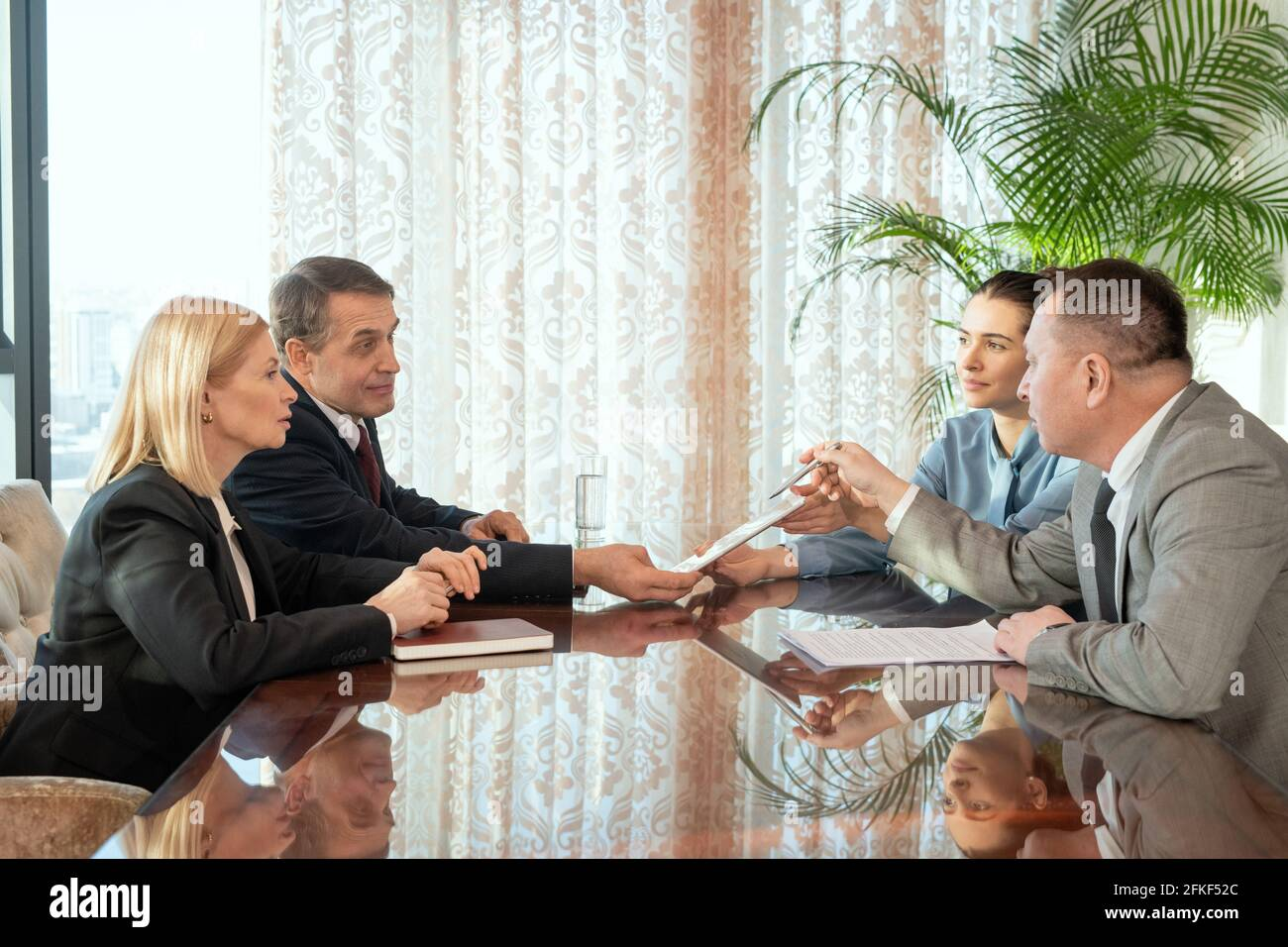Un groupe de personnes assis autour d'une table et ayant discussion Banque D'Images