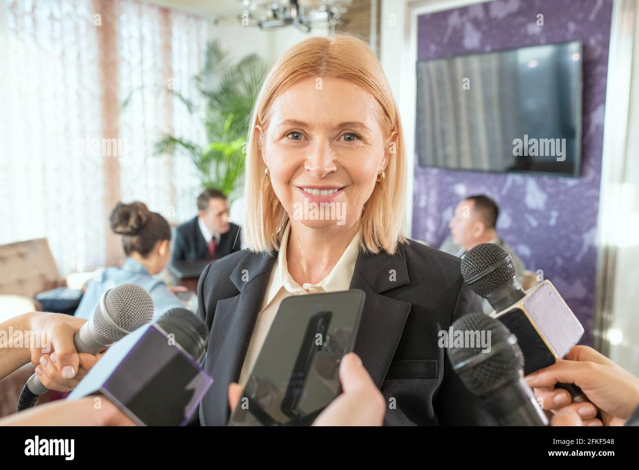 Une femme qui parle dans le microphone lors d'une conférence en face de appareil photo Banque D'Images