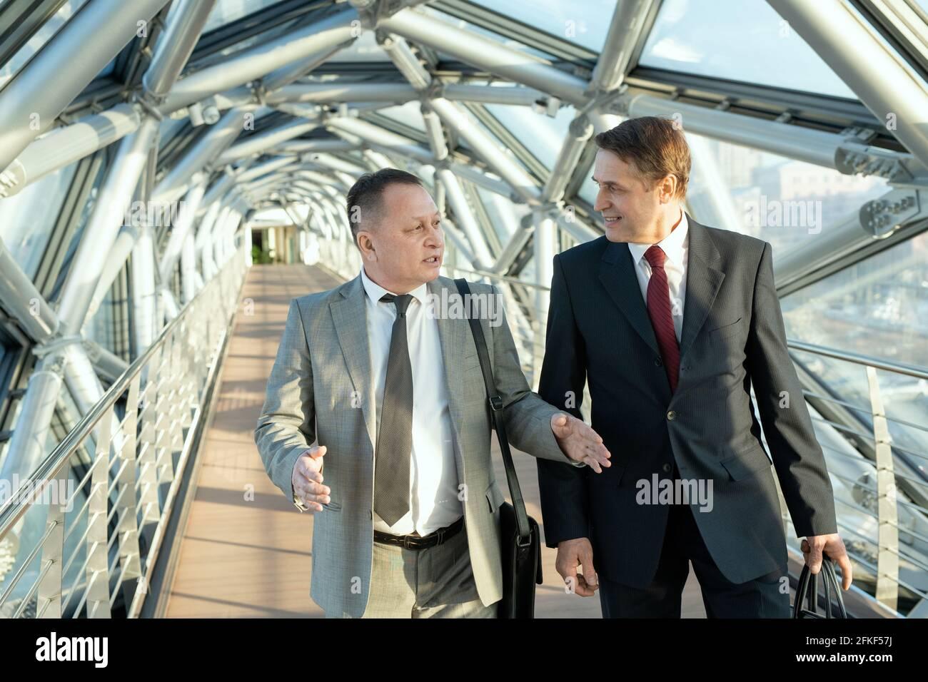 Deux hommes d'affaires confiants en costume marchant le long de bâtiment moderne Banque D'Images