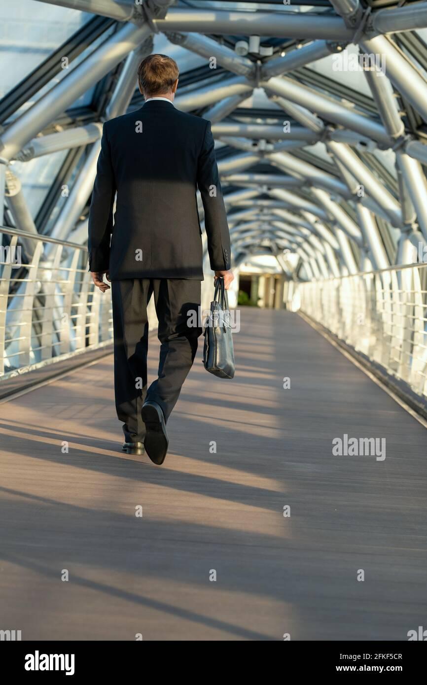 Dos d'homme d'affaires avec sac à main en cuir noir marchant vers le bas d'un longue passerelle Banque D'Images