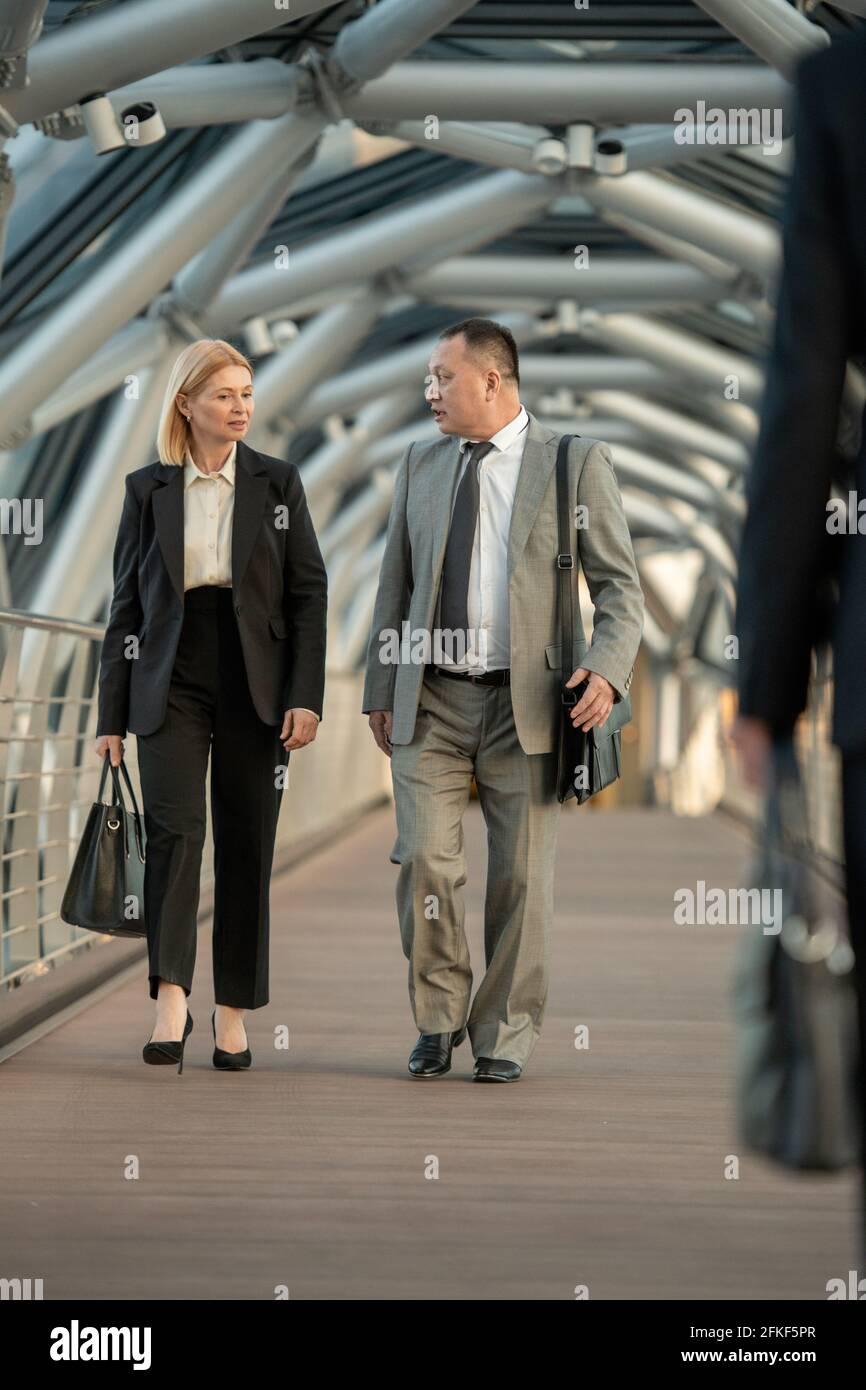 Un homme et une femme en tenue de cérémonie discutant des termes du contrat en déplacement Banque D'Images
